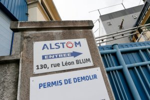 A sign with the logo of French train maker Alstom is seen near the entrance of the Alstom production site in Villeurbanne
