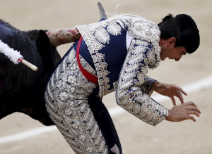 Spanish assistant bullfighter Marco Galan is tackled by a bull during a bullfight at the Ventas bullring in Madrid June 7, 2015.   REUTERS/Javier Barbancho - RTX1FJNH