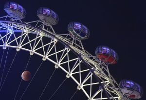 a-supermoon-is-seen-during-a-lunar-eclipse-behind-pods-of-the-london-eye-wheel-in-london_5426935