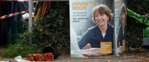 Flowers are layed next to an election campaign poster of the candidate for mayor's election Henriette Reker near the place where she was attacked by a man in Cologne, western Germany, on October 17, 2015. The crossbench candidate Henriette Reker was stabbed by a man and seriously injured while canvassing on the eve of the elections. AFP PHOTO / DPA / OLIVER BERG GERMANY OUT
