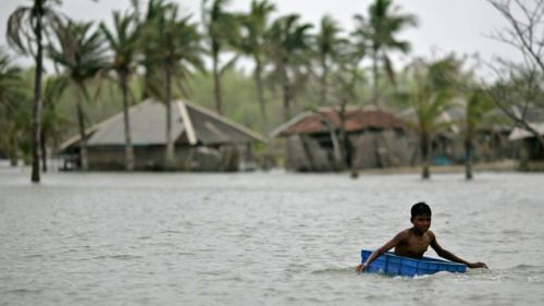 a-boy-uses-a-plastic-container-to-float-in-floodwaters-during-high-tide-in-gabura_5469880
