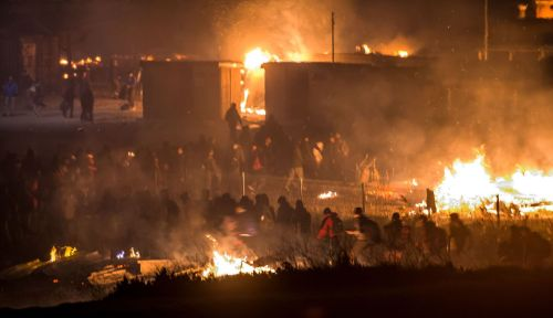 des-migrants-evacuent-le-camp-en-feu-le-10-avril-2017-a-grande-synthe_5859949.jpg